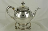Zilveren theepot op onderzetter